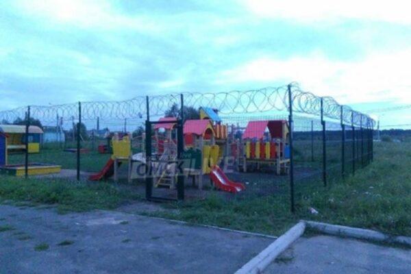 Детскую площадку огородили высоким забором с колючей проволокой